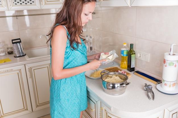Jonge huisvrouw die het diner voorbereidt dat boven het fornuis staat en ingrediënten toevoegt aan een pot die kookt op de hete plaat, zijaanzicht
