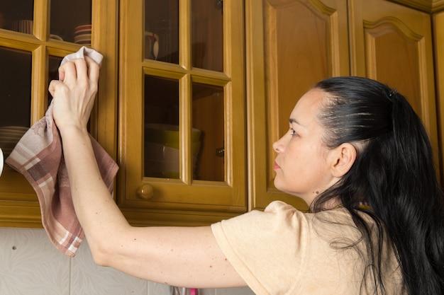 Jonge huisvrouw die keuken kast schoonmaken
