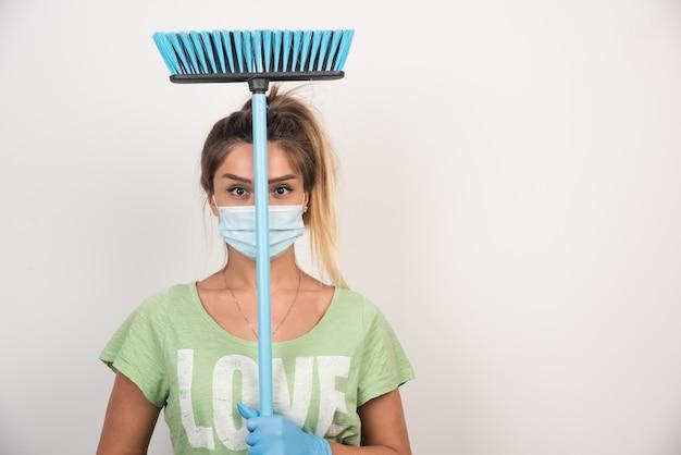Jonge huisvrouw die met de bezem van de gezichtsmaskerholding terwijl voor op witte muur kijkt.