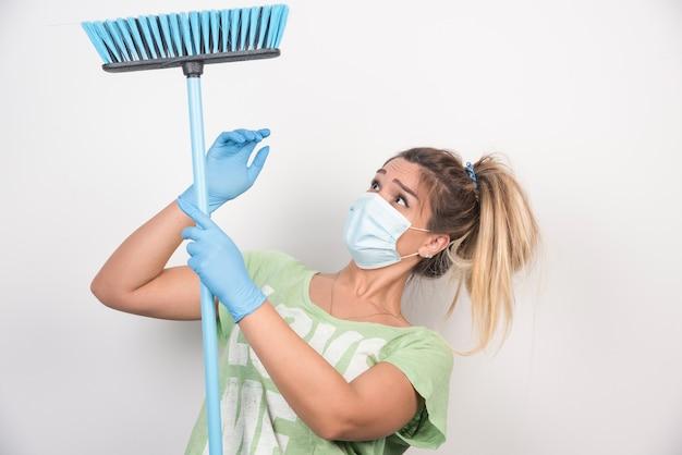 Jonge huisvrouw die met gezichtsmasker bezem bekijkt.