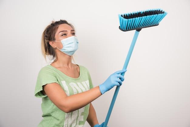 Jonge huisvrouw die met gezichtsmasker bezem op witte muur bekijkt.