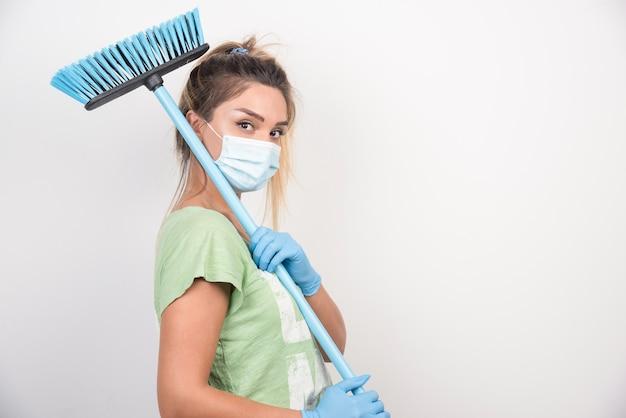Jonge huisvrouw die met gezichtsmasker en bezem voorzijde kijkt.