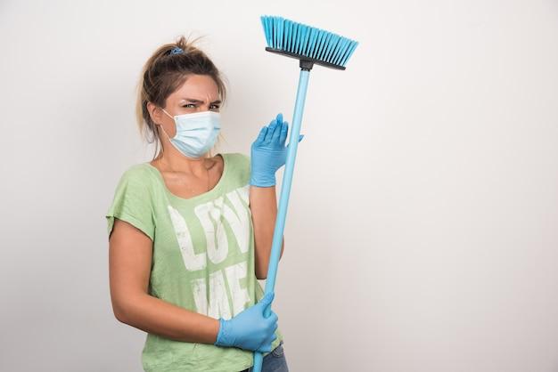 Jonge huisvrouw die met gezichtsmasker en bezem voorzijde met verwarde uitdrukking op witte muur kijkt.