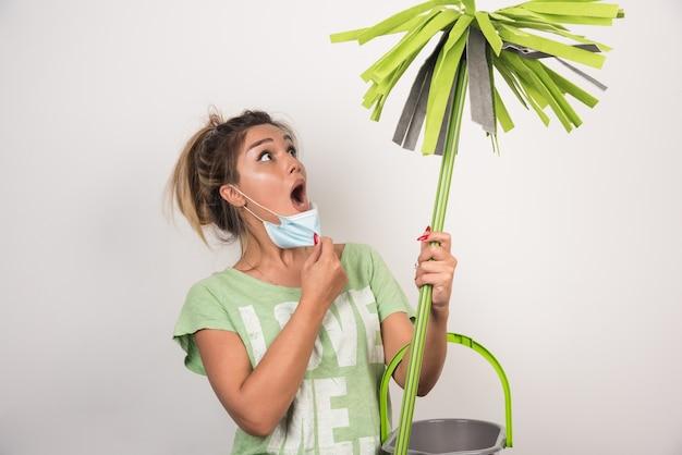 Jonge huisvrouw die met gezichtsmasker schrikbarend zwabber op witte muur bekijken.