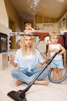 Jonge huisvrouw en kinderen beoefenen yoga op de strijkplank. vrouw met kinderen vrije tijd thuis samen. vrouwelijke persoon met dochter en zoon die plezier hebben in hun huis