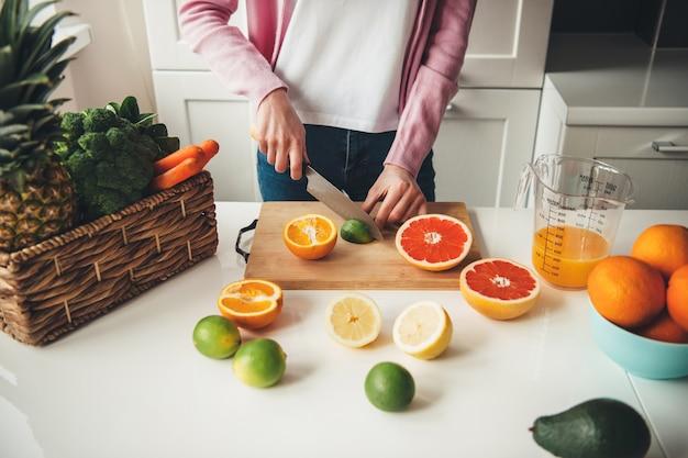 Jonge huisvrouw fruit op tafel snijden terwijl het thuis maken van vers sap