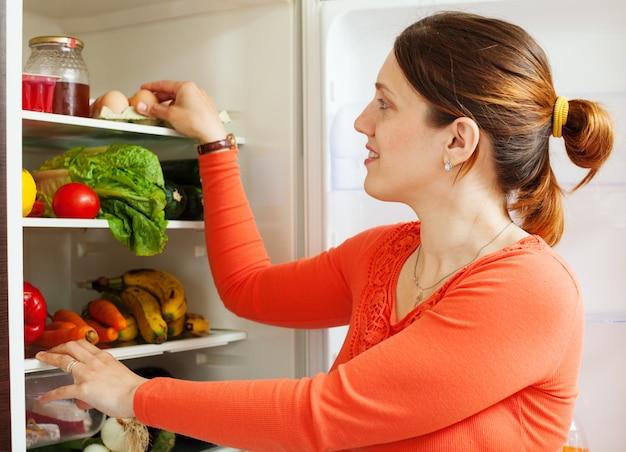 Jonge huisvrouw in de buurt van refrigerato