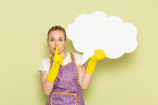 Jonge huisvrouw in overhemd en gekleurde cape die gele handschoenen dragen die wit teken houden dat stilte teken toont op groen