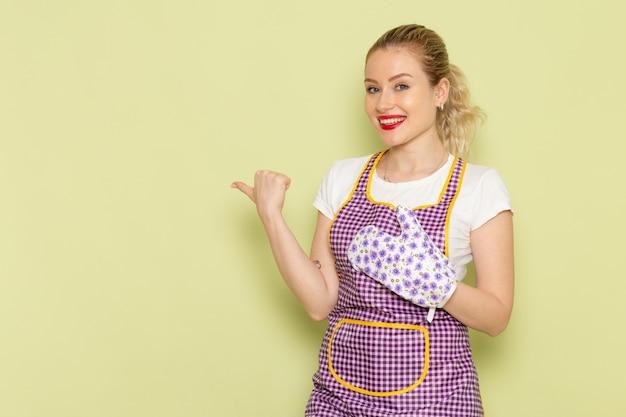 Jonge huisvrouw in overhemd en gekleurde cape glimlachend en wijzen op groen