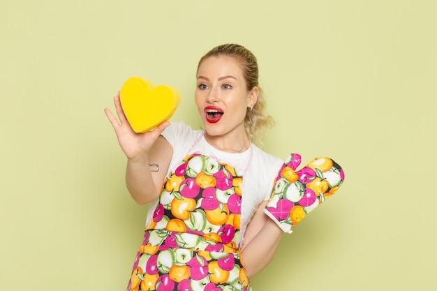 Jonge huisvrouw in overhemd en gekleurde cape hartvorm geel op groen te houden