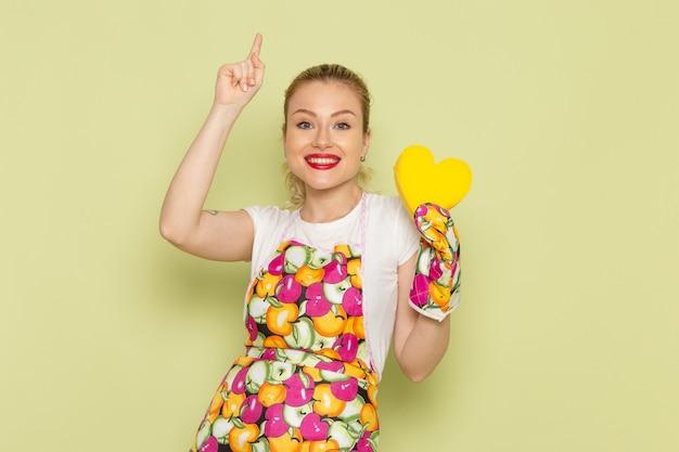 Jonge huisvrouw in overhemd en gekleurde cape met geel hartteken op groen