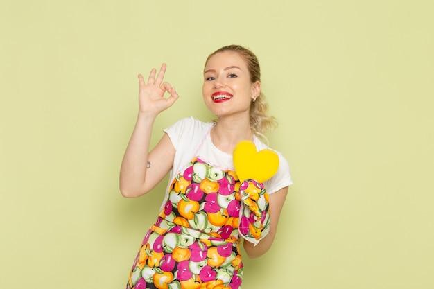 Jonge huisvrouw in overhemd en gekleurde cape met gele hartvorm glimlachend op groen