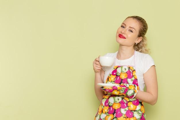 Jonge huisvrouw in overhemd en gekleurde cape met witte kopje thee glimlachend op groen