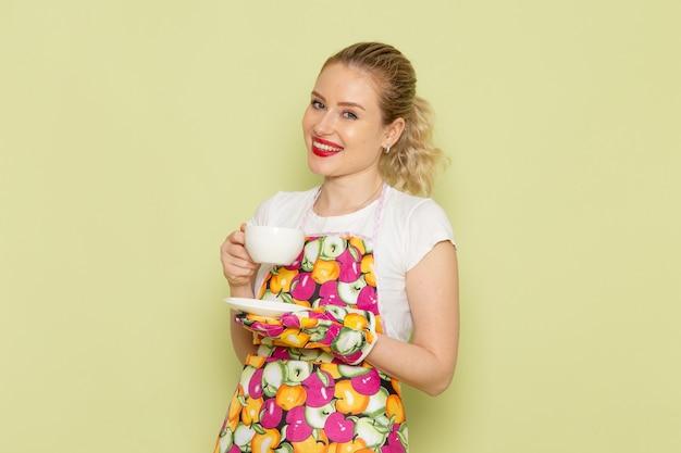 Jonge huisvrouw in overhemd en gekleurde cape met witte kopje thee op groen