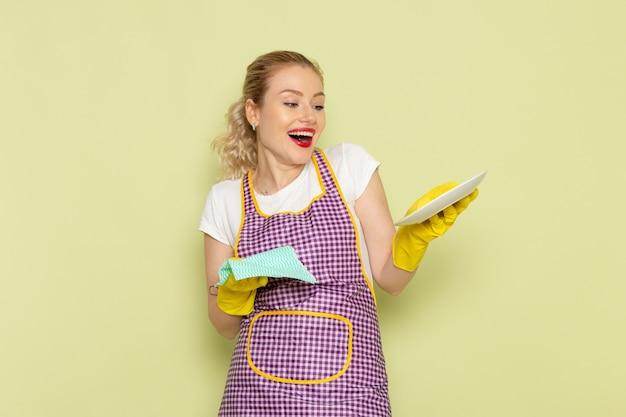 Jonge huisvrouw in overhemd en paarse cape gele handschoenen drogen plaat op groen
