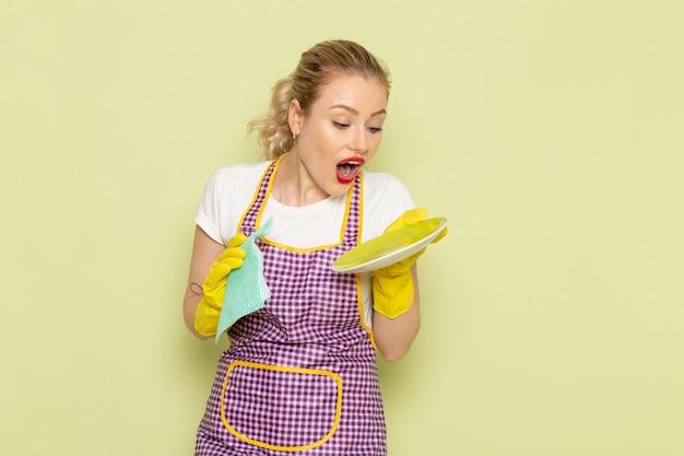 Jonge huisvrouw in overhemd en paarse cape gele handschoenen drogen platen op groen