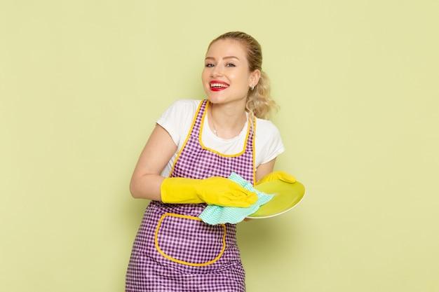 Jonge huisvrouw in overhemd en paarse cape met gele handschoenen drogen plaat op groen