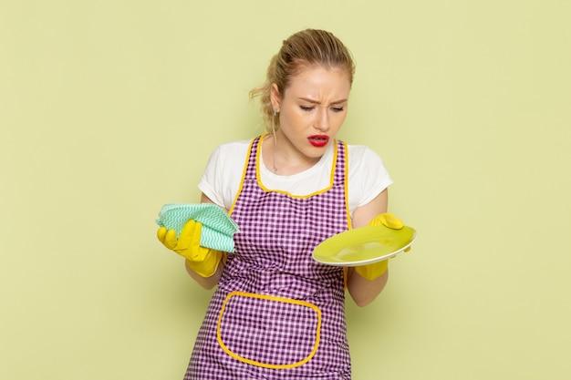 Jonge huisvrouw in overhemd en paarse cape met gele handschoenen met groene doek drogen een plaat op groen