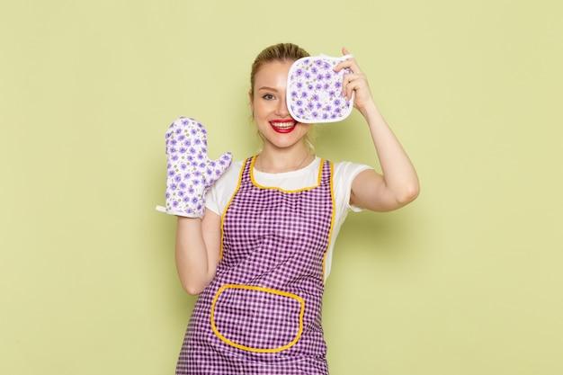 Jonge huisvrouw in overhemd en paarse kaap handschoenen poseren met een glimlach op groen