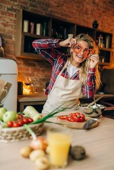 Jonge huisvrouw in schort verwent zich met rode peper