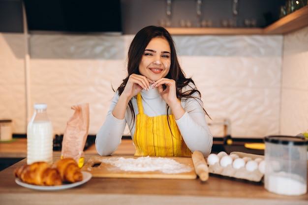 Jonge huisvrouw koken taart koekjes cake. de mooie vrouw bakt in de keuken.