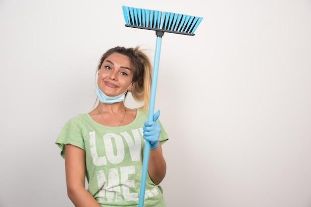 Jonge huisvrouw met de bezem van de gezichtsmaskerholding gelukkig op witte muur.