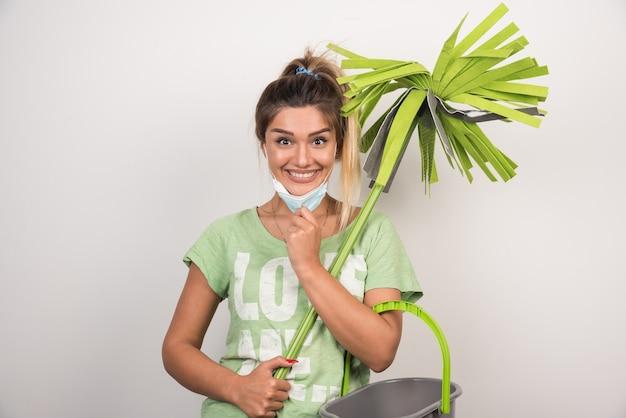 Jonge huisvrouw met de dweil van de gezichtsmaskerholding met gelukkige uitdrukking op witte muur.