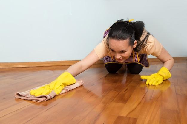 Jonge huisvrouw met gele handschoenen die de vloer schoonmaken