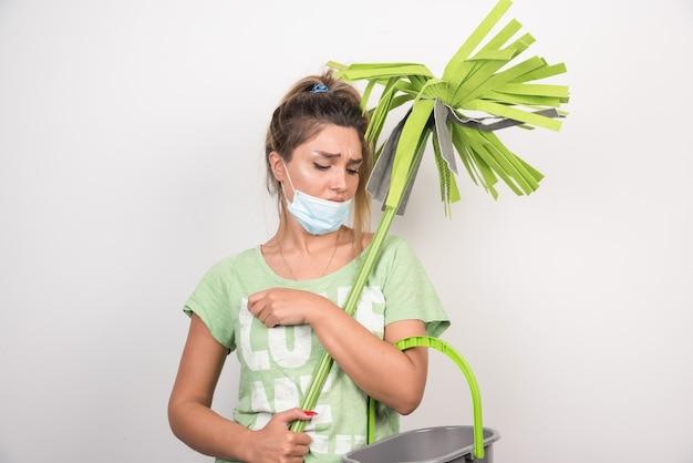 Jonge huisvrouw met gezichtsmasker die dweil houdt en ernaar kijkt.