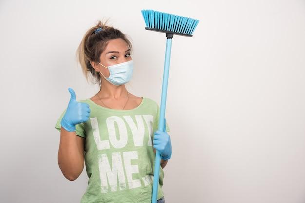 Jonge huisvrouw met gezichtsmasker en bezem die duimen maken ondertekent omhoog op witte muur.