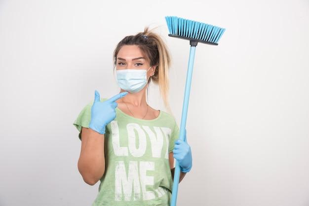 Jonge huisvrouw met gezichtsmasker en bezem die duimen omhoog teken maken.