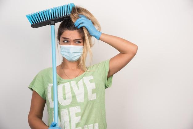 Jonge huisvrouw met gezichtsmasker en bezem die haar haar op witte muur houden.