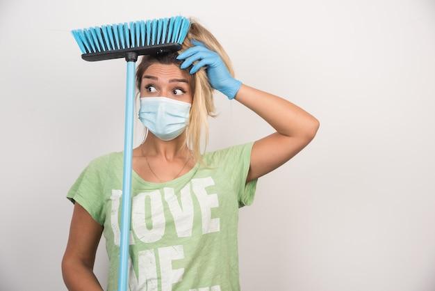 Jonge huisvrouw met gezichtsmasker en bezem kijkt verward op witte muur.