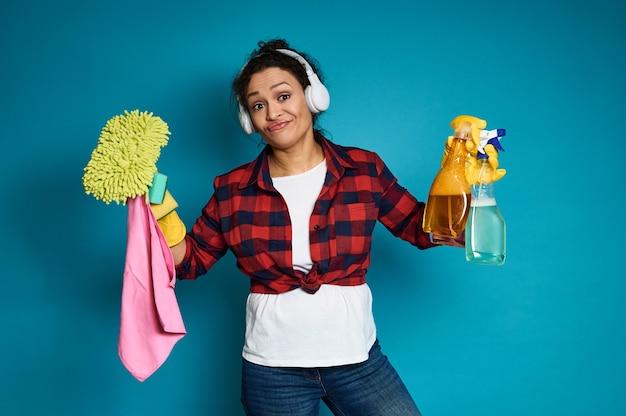 Jonge huisvrouw met het schoonmaken van hulpmiddelen en producten in de handen tegen blauw met exemplaarruimte