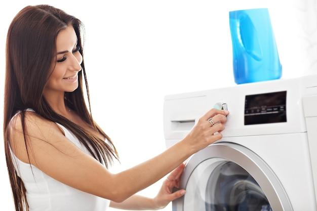 Jonge huisvrouw met was naast wasmachine washing