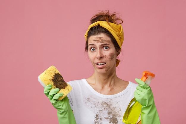 Jonge huisvrouw op zoek verrast met ontevreden uitdrukking