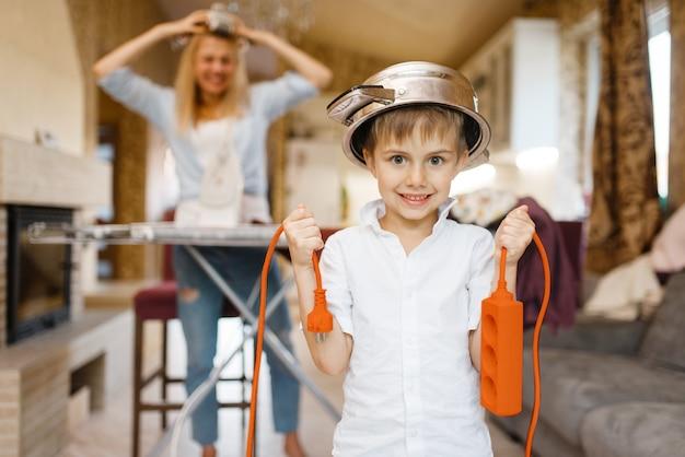 Jonge huisvrouw strijkt de kleren, kleine jongen ploetert met elektriciteit. vrouw doet huishoudelijk werk thuis. vrouwelijk persoon met haar speelse zoon in huis