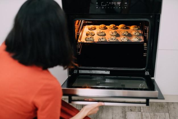 Jonge huisvrouw zelfgemaakte koekjes maken in de keuken