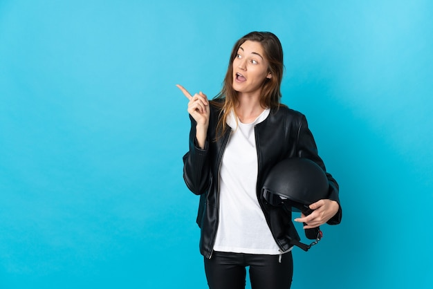 Jonge ierse vrouw met een motorhelm geïsoleerd op een blauwe achtergrond met de bedoeling de oplossing te realiseren terwijl ze een vinger opheft