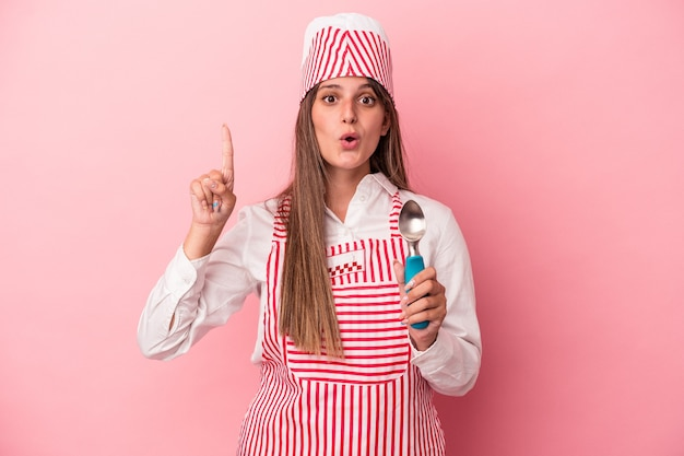 Jonge ijs maker vrouw met lepel geïsoleerd op roze achtergrond met een geweldig idee, concept van creativiteit.
