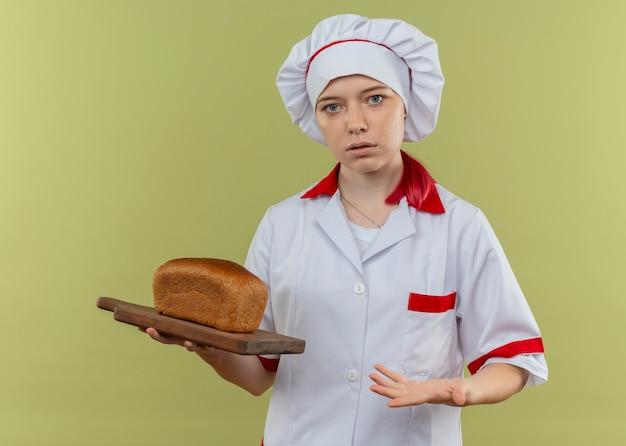 Jonge in beslag genomen blonde vrouwelijke chef-kok in uniform chef-kok houdt brood op snijplank en houdt de hand open geïsoleerd op groene muur
