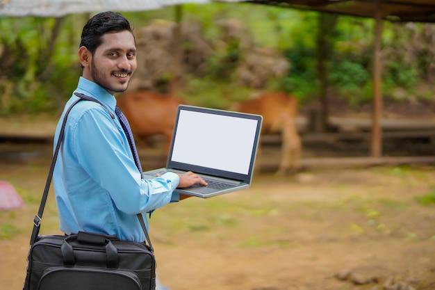 Jonge indiase agronoom of bankier die het laptopscherm toont