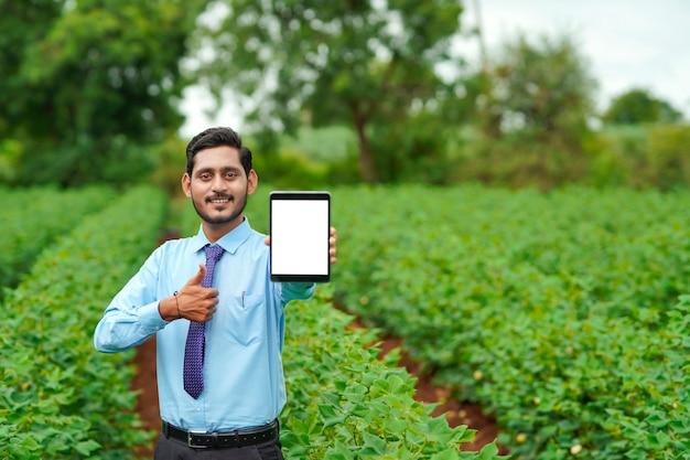Jonge indiase agronoom of officier die tablet toont op landbouwgebied.