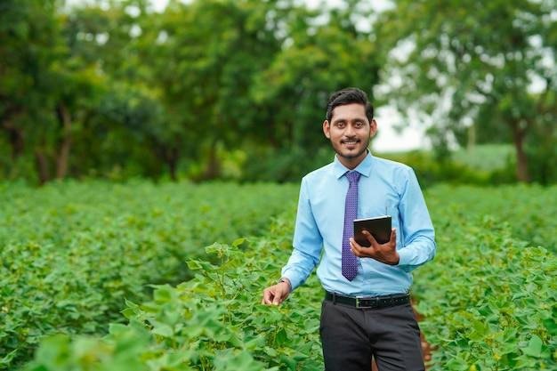 Jonge indiase agronoom of officier met behulp van tablet op landbouwveld.