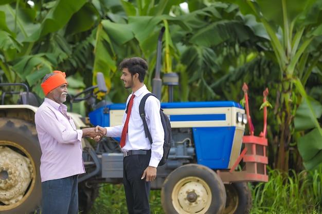 Jonge indiase agronoom shack hand met boer in veld