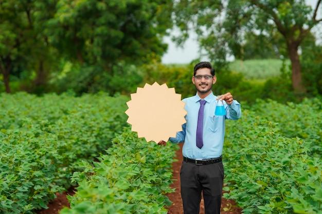 Jonge indiase agronoom toont bord met kopieerruimte op landbouwveld.