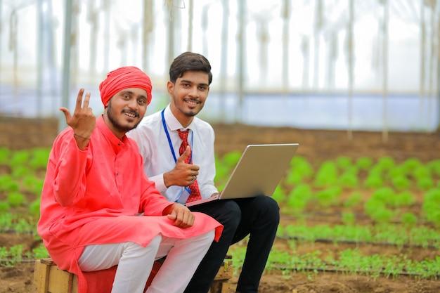 Jonge indiase agronoom wat informatie tonen aan boer in laptop op kas