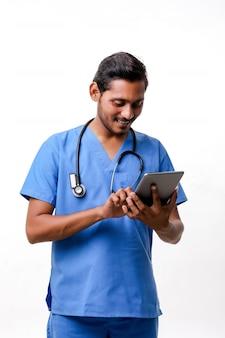 Jonge indiase arts met behulp van smartphone op witte achtergrond.