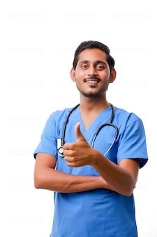 Jonge indiase arts met een stethoscoop kladblok en duimen opdagen op witte achtergrond.