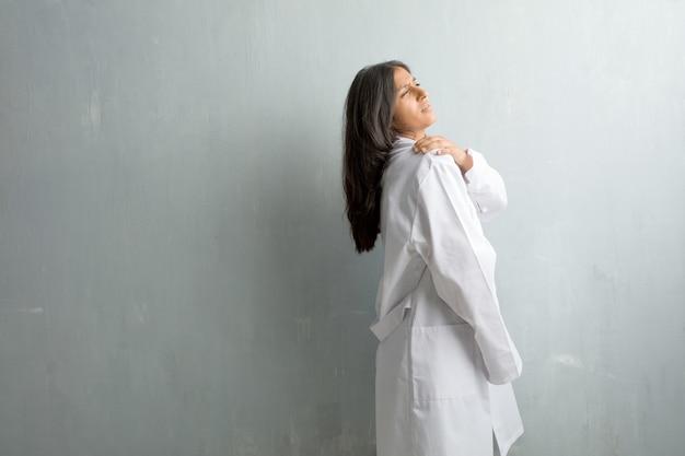 Jonge indiase arts vrouw tegen een muur met pijn in de rug als gevolg van werkstress, moe en slim
